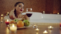 Close ups of beautiful woman clinking glasses of red wine in bath Stock Footage