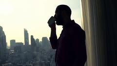 Silhouette of young man drinking coffee and admire view from window at home Stock Footage