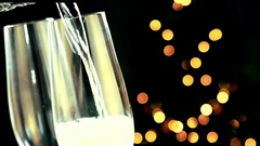 Pouring champagne into flutes with golden bubbles Stock Footage