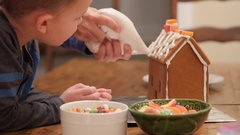 Family decorates adorable ginger bread house for christmas Stock Footage