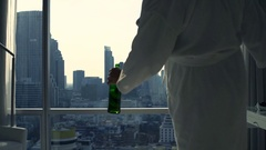 Drunk man in bathrobe drinking beer by window at home, super slow motion 120fps Stock Footage