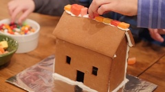 Family decorates a small ginger bread house for christmas Stock Footage