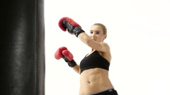 Close shot of a girl kickboxer which kicking punching bag Stock Footage
