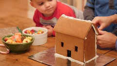 A family decorating a small ginger bread house for christmas Stock Footage