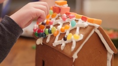 Family decorating adorable ginger bread house for christmas night Stock Footage