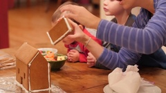 A family decorating a small ginger bread house Stock Footage