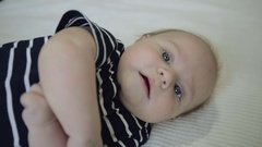 Close up. Little baby lying on side and turned over on back. Stock Footage