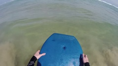Man jumping and swimming on body board Stock Footage