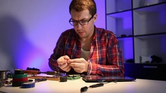 The wizard verifies the solder on the circuit board with a magnifying glass with Stock Footage