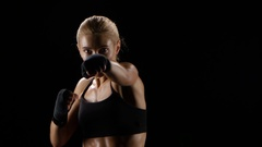Boxer girl makes blows by hands and by feet Stock Footage