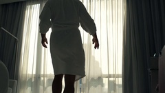 Man in bathrobe unveil curtains and admire view from window, super slow motion  Stock Footage