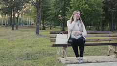Beautiful pregnant woman communicates by phone for a walk in the park. Stock Footage