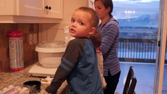 Kids making icing with their mother in the kitchen Arkistovideo