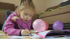 Portrait of little girl while lying and painting on the carpet by Sheyno. Stock Footage