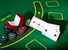 Casino chips and a precious ring on green poker table background, man throws Stock Photos
