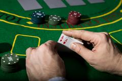 Poker playing card on a green table background, man holding two aces Stock Photos