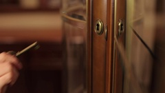 The girl opens an antique brass key glass door. Stock Footage