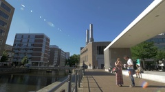 View of modern city buildings and tourists walking about canal, Rotterdam Stock Footage