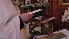 Priest reads from the book Stock Footage