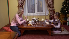 Mother and daughter eating biscuits in a cafe Stock Footage