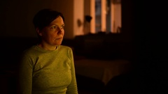 Woman watching TV program with flashing images in dark room Stock Footage