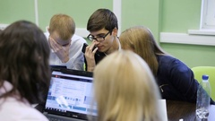 Group of students in a classroom. Young guy with glasses communicate with his Stock Footage