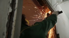 A man destroying old door frame with an angle grinder. Repairman, master Stock Footage
