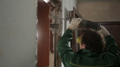 Worker using drill for dismantling old door Stock Footage