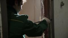 Hands of worker who dismantles old door frame using crowbar Stock Footage