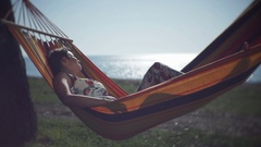 Cute girl enjoying leisure in a hammock on the sea background Stock Footage