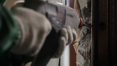 Worker using drill for dismantling old door Arkistovideo