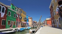 Many relaxed people strolling in colorful streets on Burano island, summer rest Stock Footage