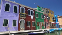 Brightly colored houses and boats at mooring points along canal on Burano island Stock Footage