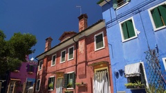 Old shabby multicolored houses, flowers growing in sunny street, Burano island Stock Footage