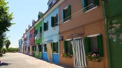 Shabby house neighboring nice multicolored buildings, colorful street on Burano Stock Footage