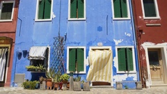 Many flowers growing in pots near shabby blue house, Burano island architecture Stock Footage