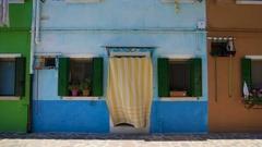 Nice blue home in multicolored street of Burano island, cozy Italian house Stock Footage