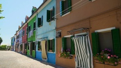 Nice houses painted in bright colors decorated with flower pots, Burano style Stock Footage