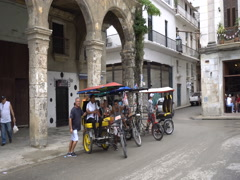 Driver with passenger leave parking zone on local taxi trishaw. Area next to Stock Footage