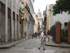 Narrow street view on pavement leading to central square with Capitol in Havana Stock Footage