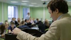 Handsome businessman in light suit giving presentation at podium Stock Footage