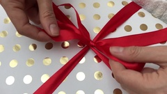 Tying and adjusting a red ribbon bow on a present Stock Footage