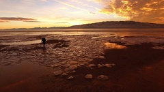 Flying over icy landscape as person walk towards colorful sunset Stock Footage