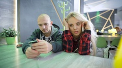 Man and woman at a table in a cafe. Girl with blond hair talking animatedly on Stock Footage