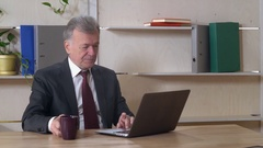 Elderly director use laptop at work Stock Footage