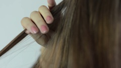 Hairdresser straightening long brown hair with hair irons - closeup Stock Footage