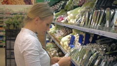 Woman in a supermarket at the vegetable shelf shopping Stock Footage