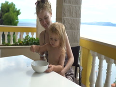 Mother with her baby eating rice porridge on the terrace at home near the sea. Stock Footage