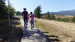 Two teen girls having fun hiking on mountain wooden walkway, running, jumping Stock Footage