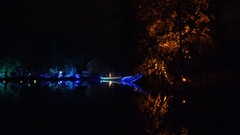 Reflections on lake water people silhouettes in lighting festival at night. 4K Stock Footage